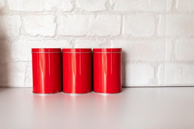 コーヒーシュガーと紅茶の赤い瓶は白いテーブルの上に立ちます。白いレンガでキッチンのデザイン。コピースペース