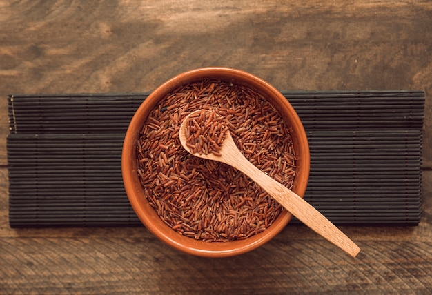 Red jasmine rice grains bowl against wooden backdrop
