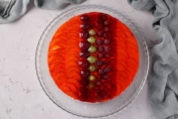 灰色の背景にフルーツとサワークリームと赤いゼリーケーキ。フラットレイ。上から見る