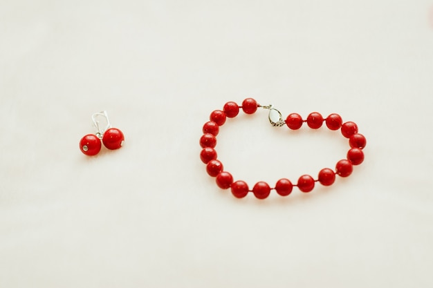 Red jewelry: bracelet and earrings with beads on a white background