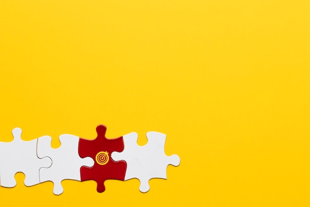 Red jigsaw puzzle piece with dartboard symbol arranged with white piece on yellow background