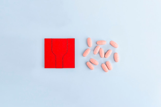 Красные кусочки головоломки с различными таблетками и лекарствами. концепция лечения неврологических заболеваний: аутизм, болезнь альцгеймера, измерение. скопируйте место для текста. день осведомленности. поддержка и принятие.