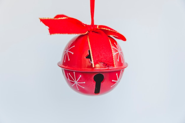 Red jingle bell with ribbon on white background