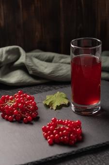 暗いテーブルの上のガラスのガマズミ属の木からの赤いジュース。ガマズミ属の果実と亜麻布の近く。健康食品。コピースペース