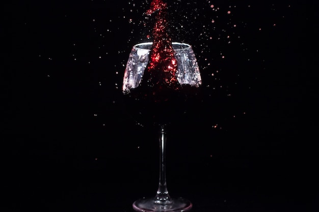 Red juice splashes in a crystal glass standing in black space