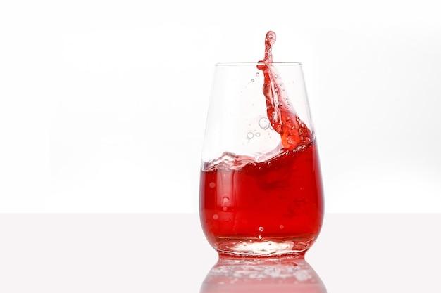 Красный сок брызгает на изолированной белой предпосылке.