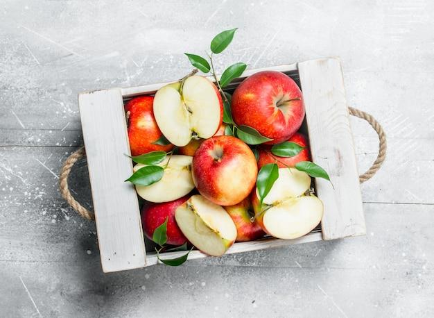 Красные сочные яблоки и дольки яблока в деревянной коробке.