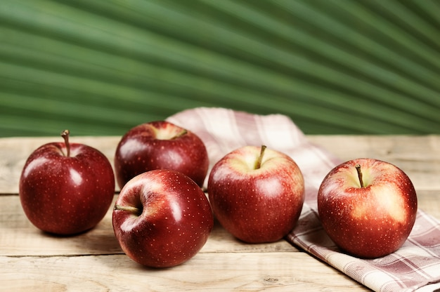 Red juicy apples on wooden background