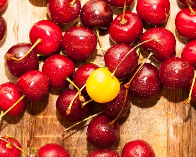 붉은 육즙 열매 익은 체리 나무 표면에 누워. 사진 근접 촬영. 작은 피사계 심도. 위에서 아래로 촬영.