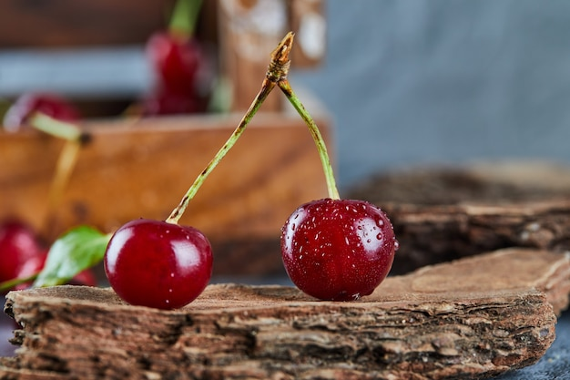 Red juicy cherry berries on a wooden piece