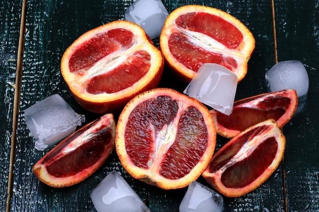 Красные сочные апельсины со льдом на темном деревянном фоне для летнего освежающего напитка
