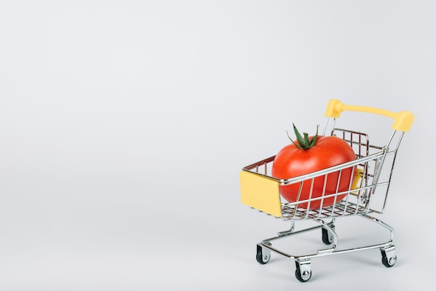 Red juicy tomato in shopping cart on white backdrop