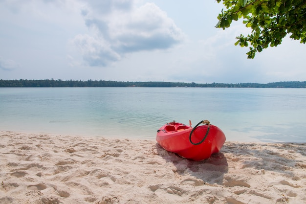 A red kayak on the beach with tropical sea