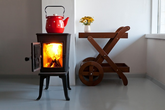 Red kettle boiling on a retro stove in the kitchen country home design with furnace at the interior