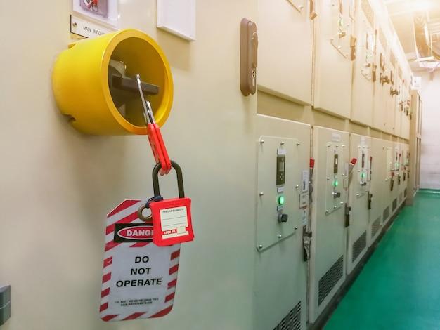 Красный ключ заблокирован и бирка для отключения электричества, номер тумблера для электрического выхода