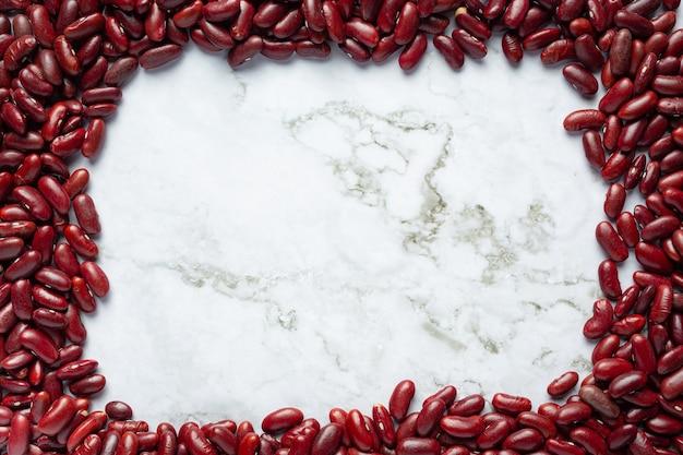 赤いインゲンマメは白い大理石の背景に配置します