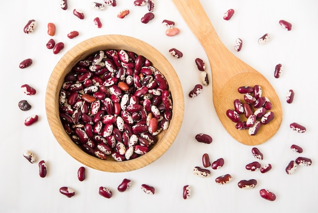 Red kidney beans. plate and spoon. white. top view