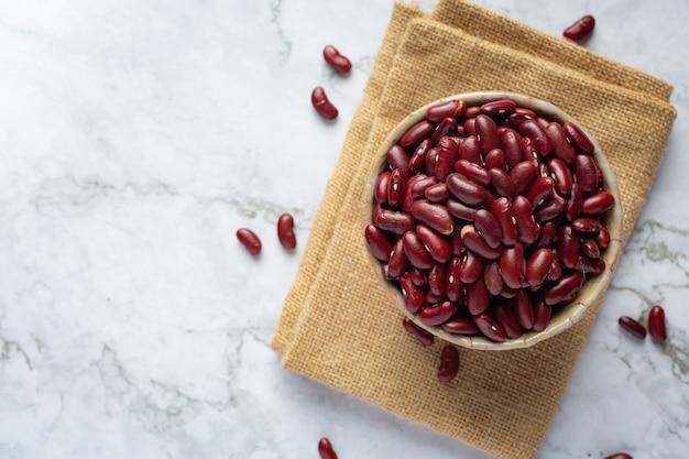 Fagioli rossi in una piccola ciotola sul tessuto del sacco