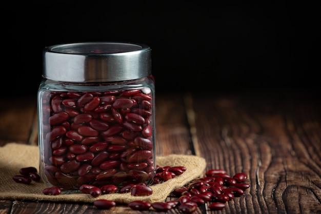 Fagioli rossi in un vasetto posto sul tessuto del sacco