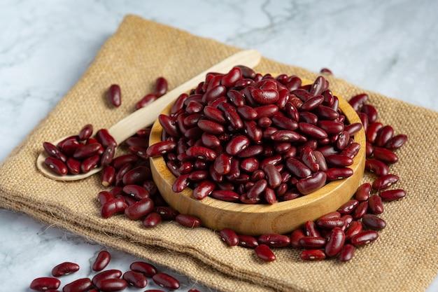 Fagioli rossi in un piccolo piatto di legno posto sul tessuto del sacco