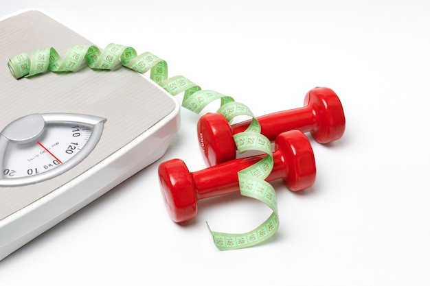 Red kilogram dumbbells, measuring tape and scales on a white background