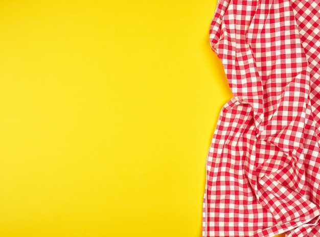 Red kitchen towel in a cage on a yellow background
