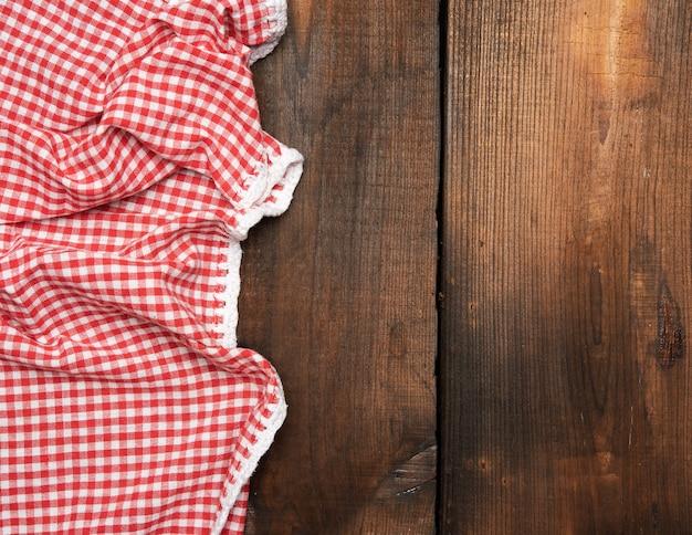 Красное кухонное полотенце на коричневой деревянной поверхности, вид сверху, копия пространства