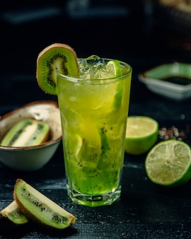 Red kiwi cocktail with lime and ice cubes.