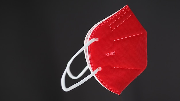 Red kn95 protective face mask on gray background.