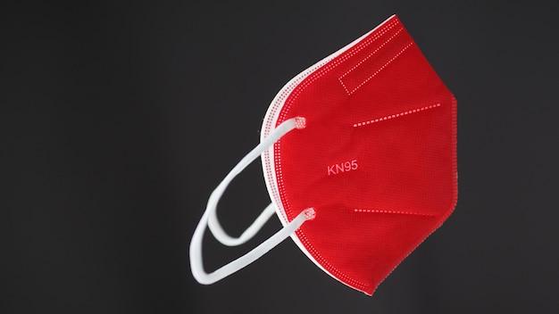 灰色の背景に赤いkn95保護フェイスマスク。