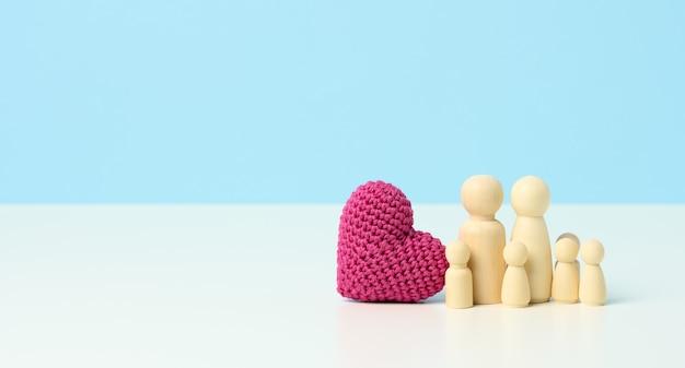 青い背景に赤いニットのハートと木製の置物の家族。家族の結束と愛、子供たちへの愛の概念