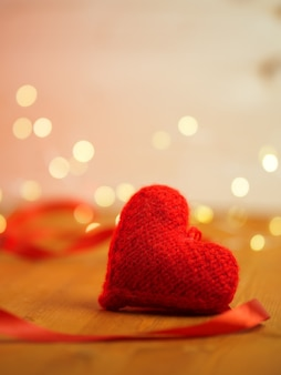 Red knitted heart symbol of love on bokeh background