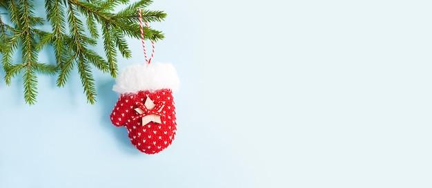 Красная вязаная варежка новогодний декор на зеленой еловой ветке