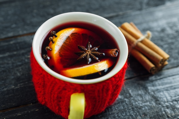 Red knitted mug of mulled wine on a dark wooden table