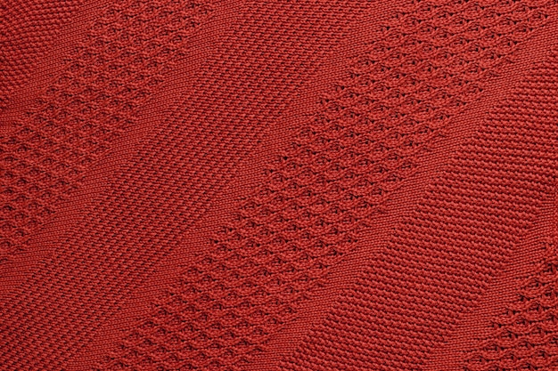 Red knitted plaid closeup.  knitted texture with diagonal ornament.  detailed warm background made of yarn.