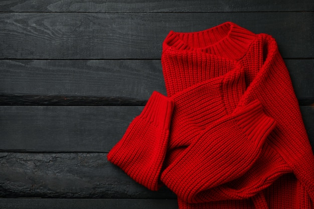 Красный вязаный свитер на деревянном столе