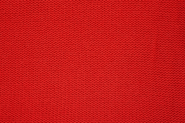 Red knitted texture. handmade knitwear. background