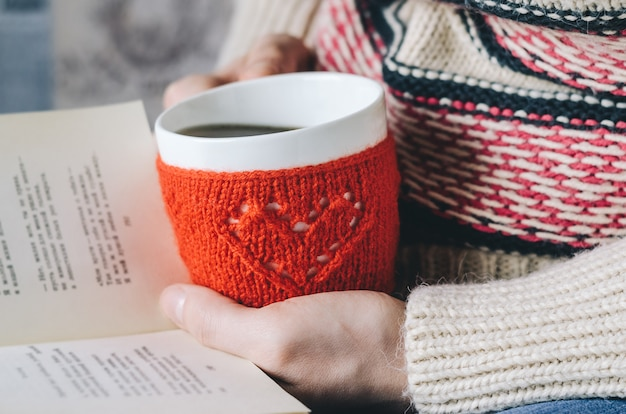 Red knitted woolen cup with heart pattern in female hands.