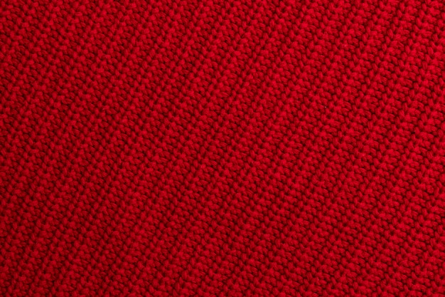 Red knitted woolen fabric background or texture