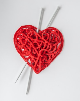 Red knitting yarn with needles, heart shaped.