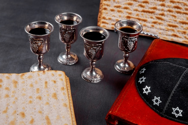 Red kosher wine four of matzah or matza passover haggadah on a vintage wood background