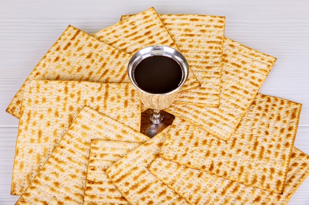 Red kosher wine with a white plate of matzah or matza and a passover haggadah