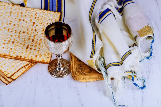 Red kosher wine with a white plate of matzah or matza and a passover
