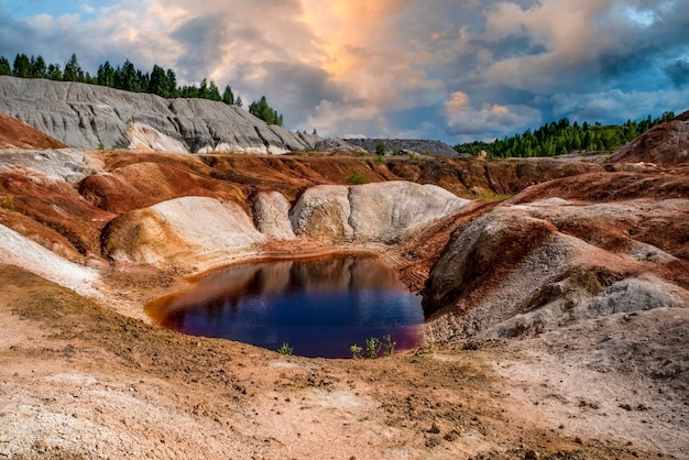 Red lake blue sky beautiful clouds landscape like a planet mars surface nature of ural mountains