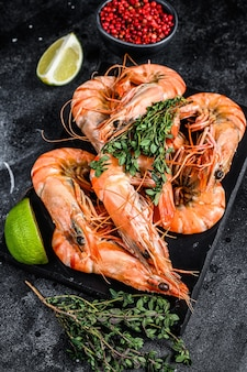 Red langostino shrimps prawns on a marble board