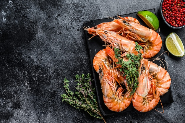 Red langostino shrimps prawns on a marble board.