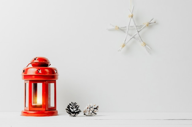 Red lantern with a candle, pine cones and star on a white background. christmas decoration