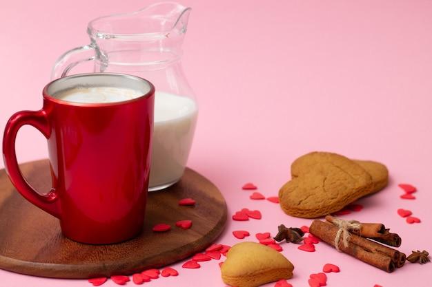Красная чашка латте и кувшин для молока с печеньем в форме сердца, корицей, анисом и красными сердечками на розовом