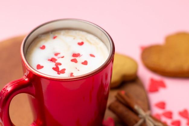 Красная чашка латте с печеньем в форме сердца, корицей, анисом и красными сердечками,