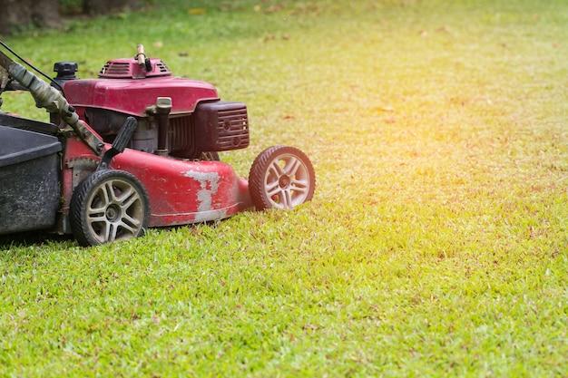 赤い芝刈り機は草を刈ります。ガーデニングの概念の背景